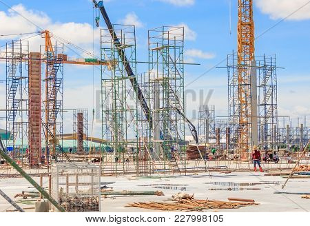 Building Construction Site, Scaffolding On A Construction Pillar At A Construction Site With Labours