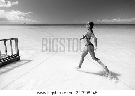 Girl With Sexy Body In Bikini Running On Beach With White Sand, Turquoise Sea And Blue Sky On Sunny