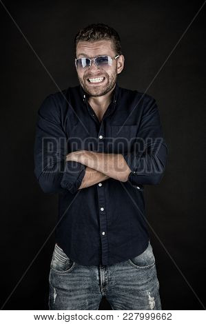 Happy Macho In Glasses, Shirt, Jeans With Folded Hands, Fashion. Man With Smile On Bearded Face On D