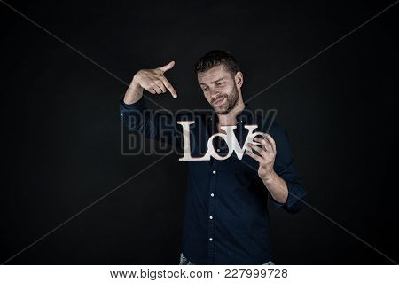 Guy Point Finger At Love Word On Dark Background. Valentines Day Concept. Love, Romance, Proposal. V