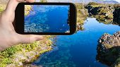 travel concept - tourist photographs water in Silfra earth crack in rift valley of Thingvellir national park in Iceland in september on smartphone poster