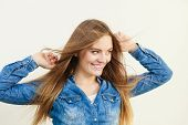 Young girl with waving hairs. Cheering woman standing in wind. Fashion coiffure leisure lifestyle concept. poster