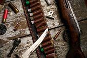 Hunting equipment riffles guns shotguns bullets knives gunpowder lead ammunition cartridges on wooden background, top view, close-up poster