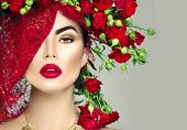 Beauty Fashion Model Girl Portrait with Red Roses Hairstyle. Red Lips. Beautiful Luxury Holiday Makeup and Hair style.  Vogue Style. Roses bouquet floristic hairstyle poster