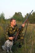Man in camouflage with a gun and russian hunting spaniel. poster