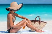Sunscreen suntan lotion spray skincare product woman putting tanning oil on her legs. Sunblock or mosquito repellent bottle spraying on body sunbathing at beach summer vacation. poster