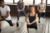 Athletic sporty diverse people doing lunge fitness exercise step forward warming up at strength training class, motivated fit multiracial group working out together at routine session in gym studio poster