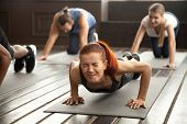 Young fit sporty woman with painful face expression doing hard difficult plank fitness exercise or push press ups feeling pain in muscles at diverse group training class in gym, endurance concept poster