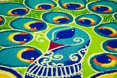 india folk art (rangoli) of a peacock using colored rice put together on the floor poster