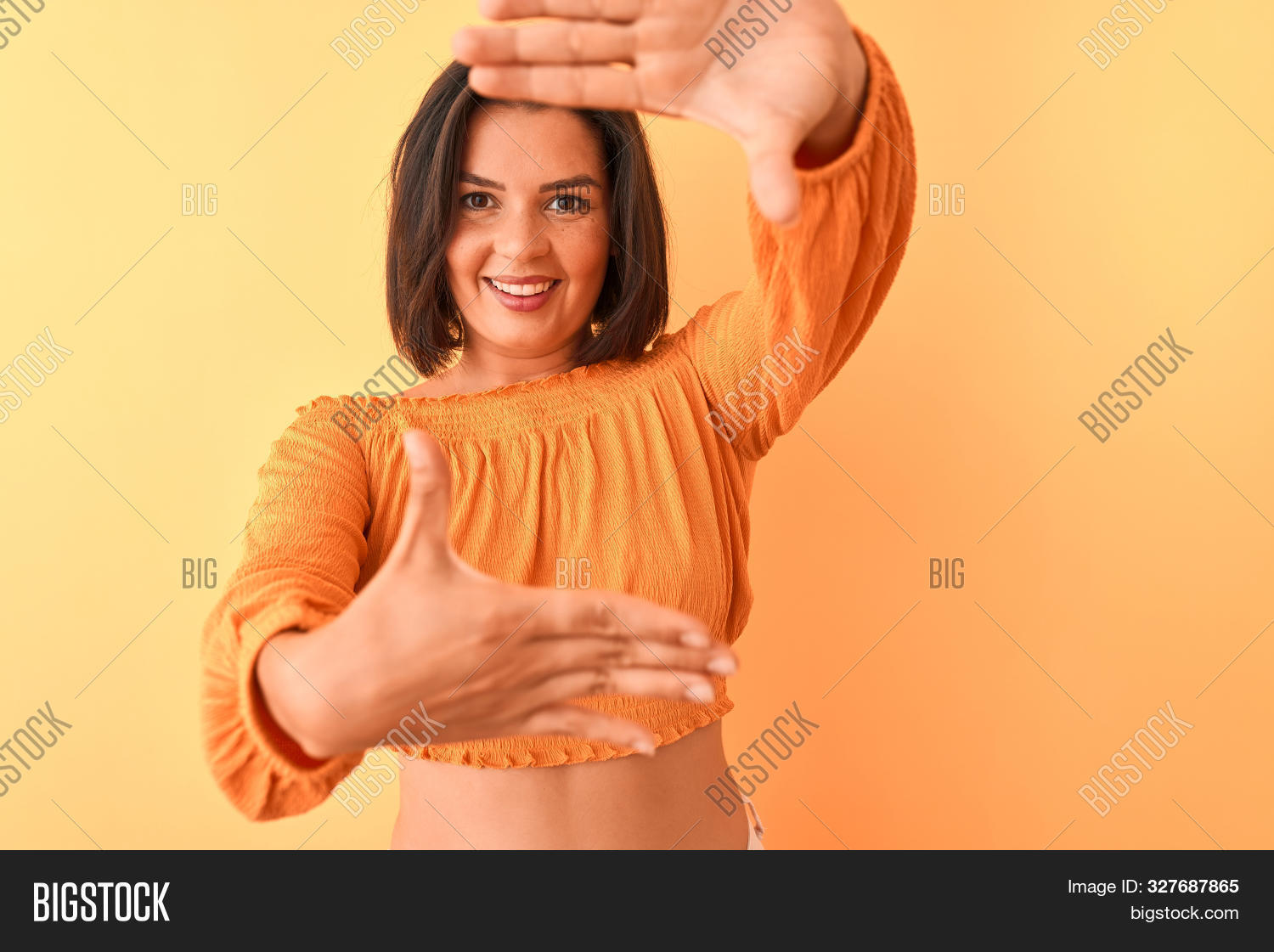 Young beautiful woman wearing casual t-shirt standing over isolated orange background smiling making frame with hands and fingers with happy face. Creativity and photography concept.