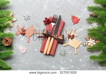 Top View Of Flatware Tied Up With Ribbon On Napkin On Cement Background. Close Up Of Christmas Decor