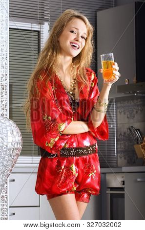 beautiful blonde woman in modern kitchen with glass of juice