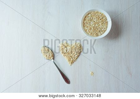Heart Of Oatmeal Oatmeal In A Plate Nearby Lies A Silver Spoon With Grits On A Light Wooden Backgrou