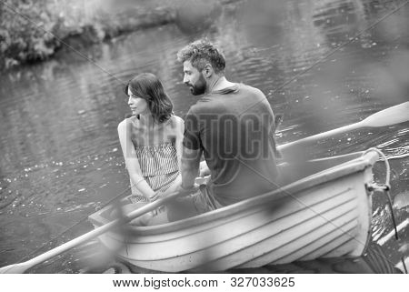 Black and white photo of  happy mid adult couple boating in lake during summer