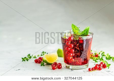 Cold Red Cocktail With Currant, Lime, Mint, Thyme And Ice In Glass On Light Gray Concrete Surface Ta