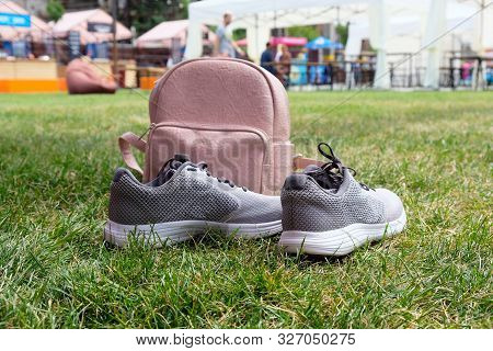 Pink Leather Female Backpack And Gray Sneakers On A Green Lawn In The Park. The Concept Of Outdoor R