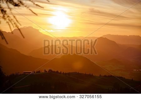 Sunset In The Austrian Alps - Panorama View From Donnerkogel, With Layers Of Mountains Peaks And Rid