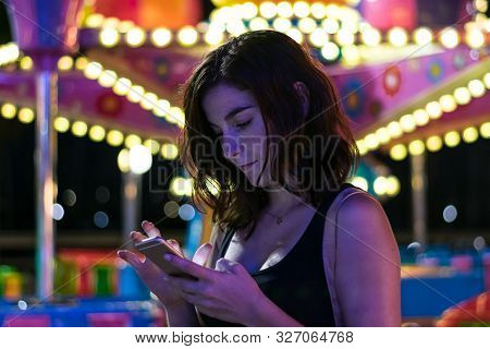 Young Woman Is Looking Her Smartphone In A Fair