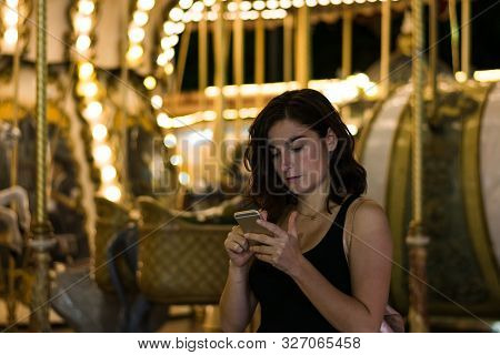 Young Woman In A Fair With Her Smartphone