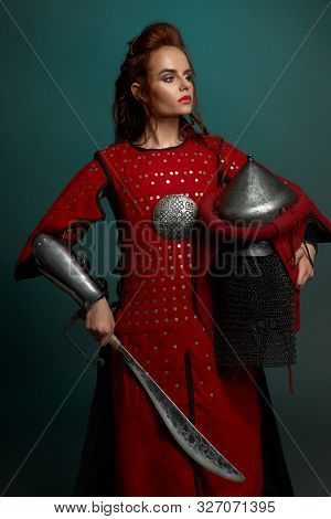 View Form Side Of Barbarian Female Fighter Posing With Helmet And Knife In Hands In Studio. Young Wa