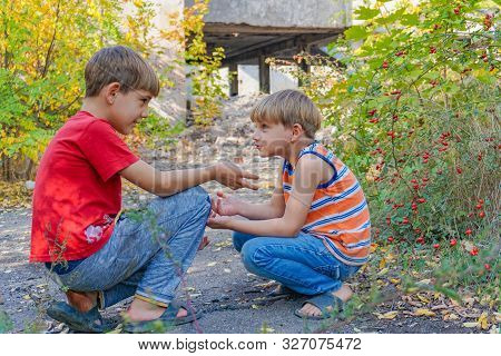 Two Boys Sit Opposite Each Other In The Park And Communicate With Each Other In Two.