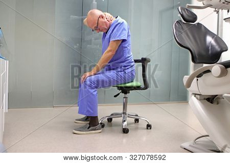 Neck pain in the dental practice.Mature dentist having short break for regeneration after long working hours in his office