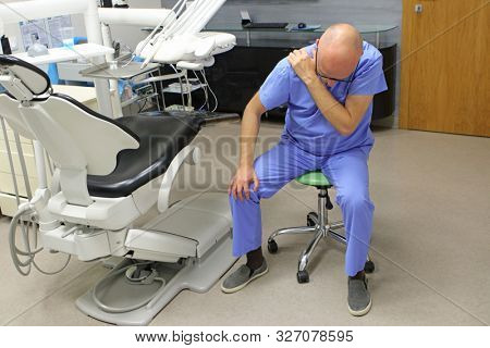 Shoulder pain in the dental practice.Mature dentist having short break for regeneration after long working hours in his office