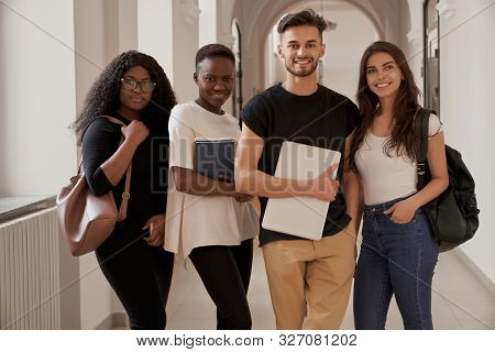 Group Of Four Mixed-race Smiling Students With Laptop, Notebook And Backpacks Looking At Camera In U