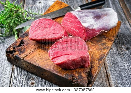Dry aged beef fillet steak natural as closeup offered on an old rustic wooden cutting board
