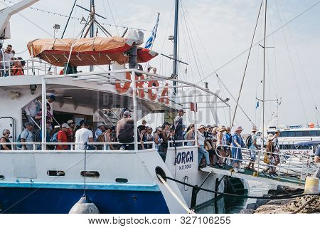 Delos, Greece- September 20, 2019: People Disembarking Delos Tours Orca Boat That Has Just Arrived T