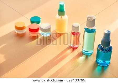 Various Toiletries In Clear Plastic Travelling Bottles On Neutral Paper Background With Long Shadows
