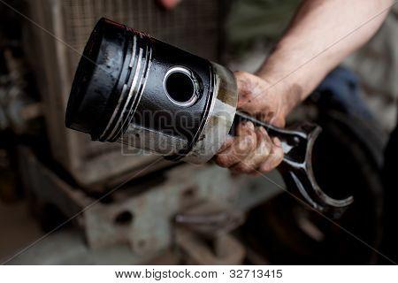 Car Mechanic Holding Piston