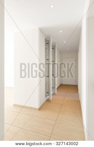 Corridor with travertine floor, white walls and built-in wardrobes. Nobody inside