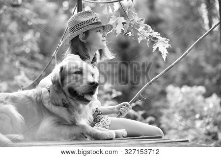 Black and white photo of Young girl fishing while sitting with dog on pier