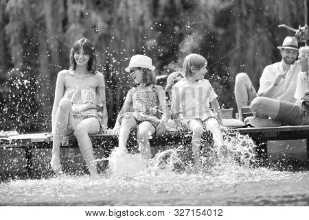 Black and white photo of mother playing water with kids in lake while sitting on pier against family at lakeshore during summer