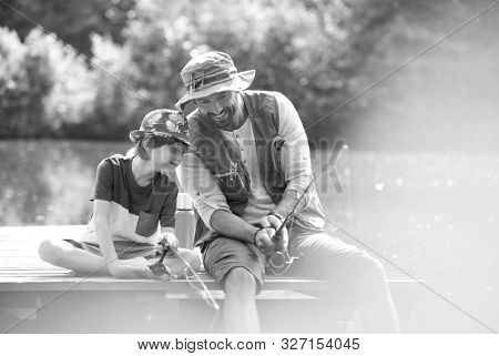 Black and white photo of father and son catching fish in pier at lakeshore