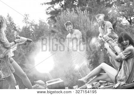 Black and white photo of couples playing water guns in per at lakeshore