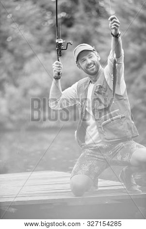 Black and white photo of happy father catching fish at lakeshore