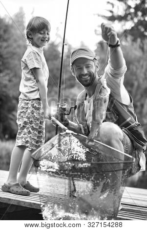 Black and white photo of Smiling father and son catching fish on pier