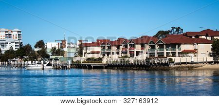 Large Waterside Houses, Apartment Condominiums In Suburban Community On Riverfront With Boat Moored