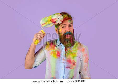 Professional Painter, Decorator, Builder Worker. Handsome Bearded Worker With Paint Roller And Hard