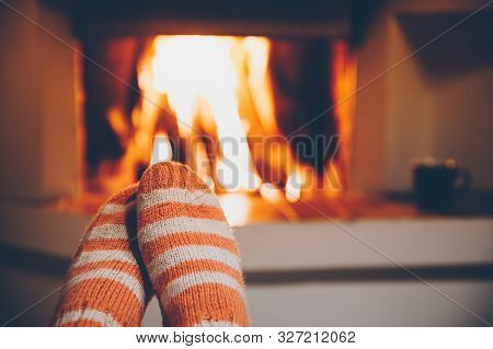 Feet In Wool Striped Socks By The Fireplace. Relaxing At Christmas Fireplace On Winter Holiday Eveni
