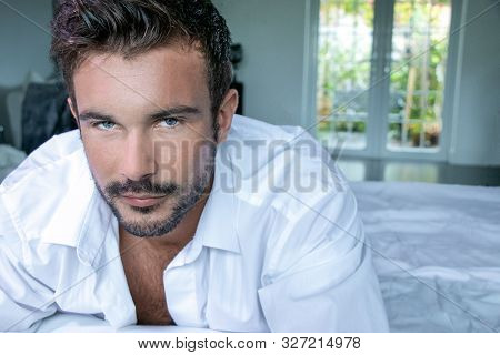 Portrait Of Handsome Man With Blue Eyes And Beard Looking At Camera With Window And Garden In Backgr