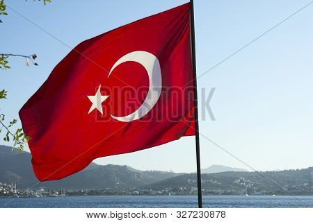 Turkish Flag Close Up. The Turkish Flag Develops Against The Blue Sky Of Mountains And The Sea.