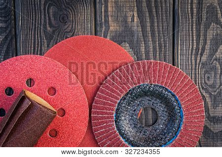 Set of abrasive tools different colors and sandpaper on black vintage wooden background poster