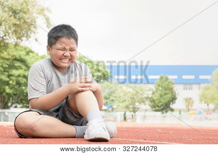 Kid Athlete Suffering Form Running Knee Or Kneecap Injury During Outdoor Workout On Track