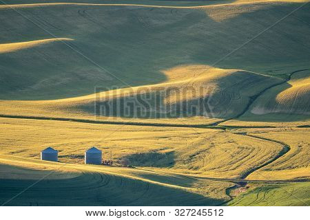 Farm Silos, Buildings And Equipment In The Rolling Hills Of The Palouse In Washington State Usa