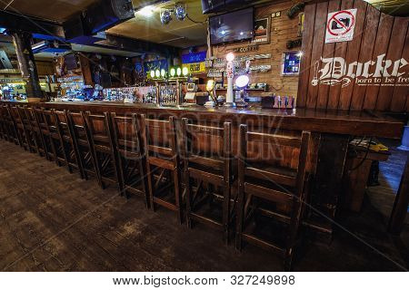 Kiev, Ukraine- March 19, 2018. Wooden Tall Chairs Lined Up Along A Bar Counter In An Irish Pub Pub.