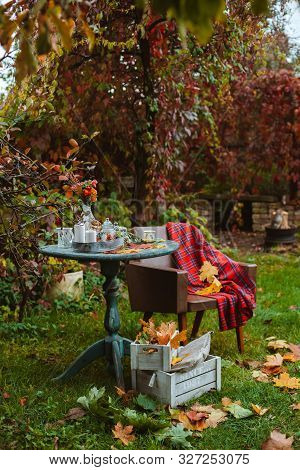 Cozy Patio. Autumn Leaves Lie On A Wooden Antique Round Table With Crockery Cups And Cookies And Can