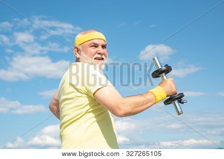 Old Mature Man Exercising With Dumbbell. Senior Sportsman In Sport Center. Health Club Or Rehabilita